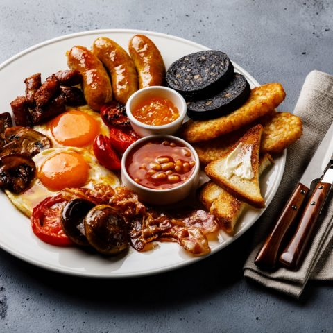 Full fry up English breakfast with fried eggs, sausages, bacon, black pudding, beans and toasts on gray concrete background